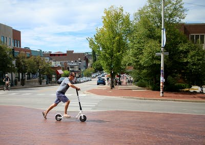 A man rides a Bird scooter at Sample Gates on Sunday. The Bird scooters are part of an electric vehicle sharing program.