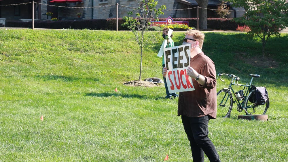 "A protester holds a sign with the message ""Fees suck"" during a protest Aug. 24 in Dunn Meadow. The Indiana Graduate Workers Coalition is calling for graduate students to boycott IU's mandatory fees."