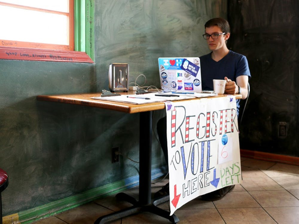 Kegan Ferguson, a senior in law and public policy, tends a voter registration booth Wednesday afternoon. Volunteers from IU Dems took shifts between 3 and 7 pm at Baked! of Bloomington on 3rd Street.