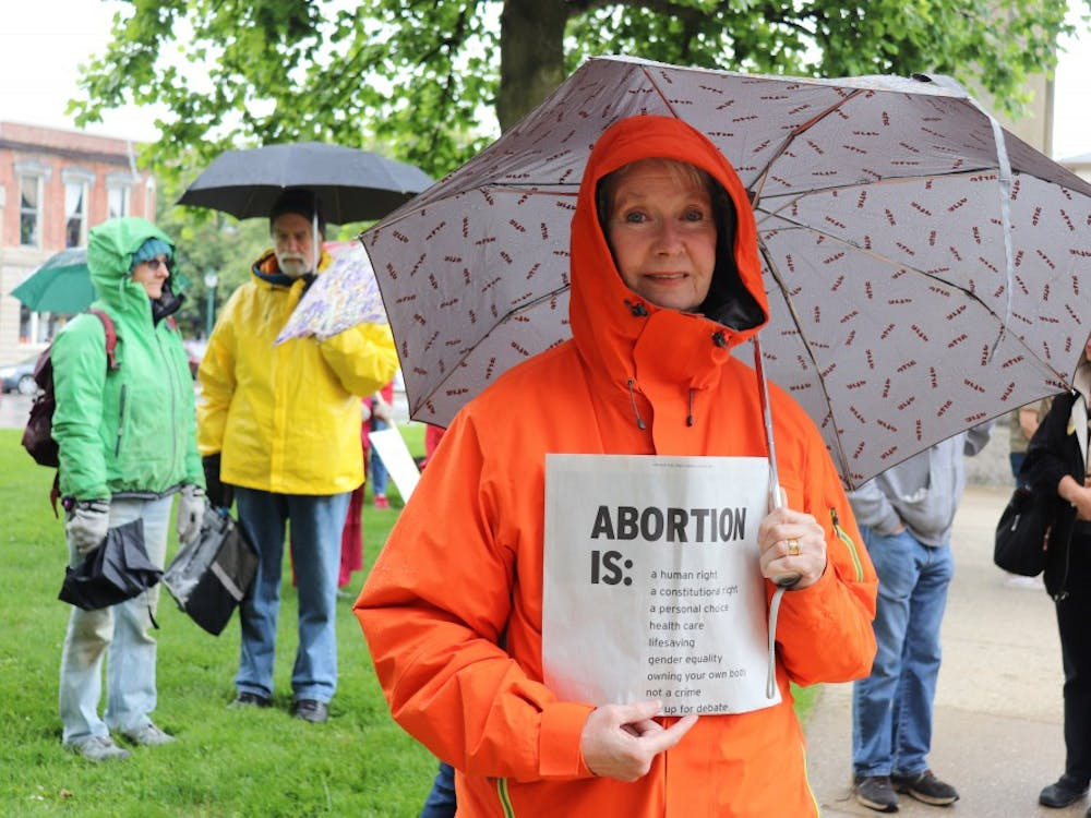 Protesters stand outside around 12 p.m. on May 21 at the Monroe County Courthouse. A woman holds a sign at the #StopTheBans rally.
