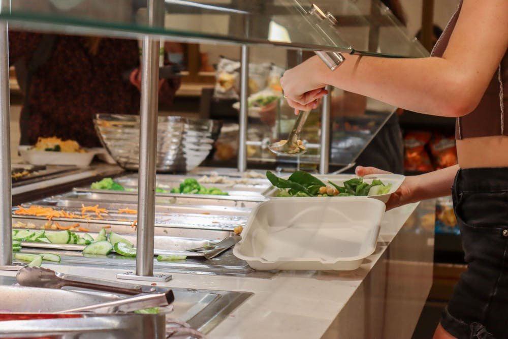 <p>A student scoops ingredients onto their salad Oct. 5, 2021, at The Mix in the Indiana Memorial Union.</p>