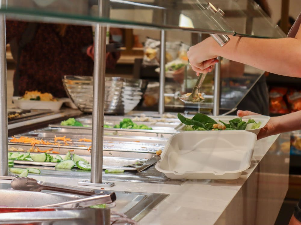 A student scoops ingredients onto their salad Oct. 5, 2021, at The Mix in the Indiana Memorial Union.