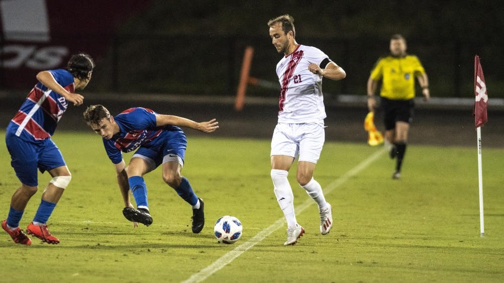 Redshirt junior Spencer Glass dribbles past a pair of DePaul defenders Aug. 24 at Bill Armstrong Stadium. The Hoosiers scored twice in the first half and once in the second half in their 3-1 win over the Blue Demons.