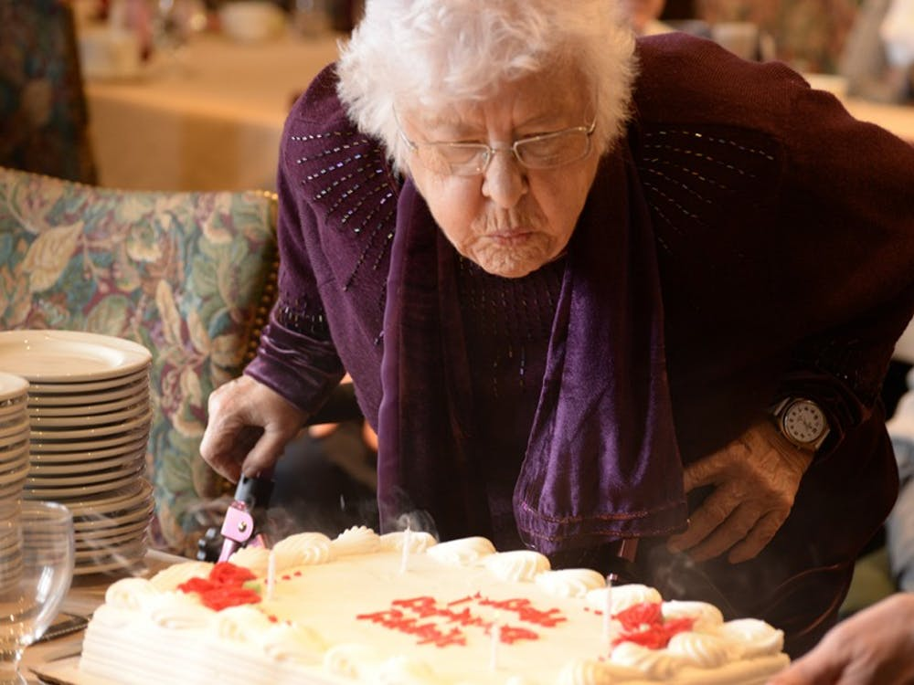 Marjorie Blewett blows out her birthday candles Monday afternoon in the Cornanation Room in the IMU. Members of the Bloomington Press Club presented her with a cake in celebration of her ninetieth birthday.