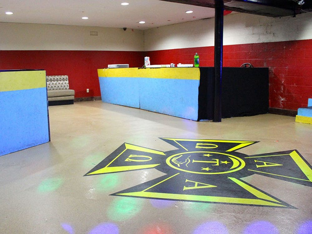 The Alpha Tau Omega basement party room displays the fraternity's seal and colors.