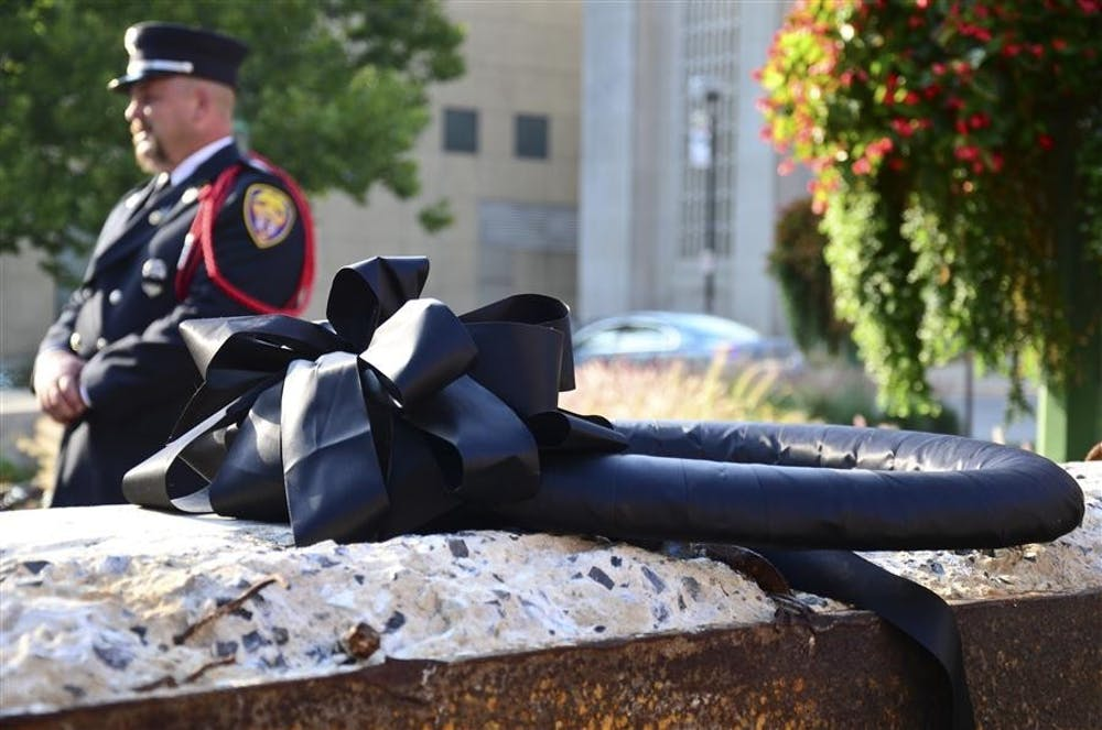 <p>Bob Loviscek, president of Metropolitan Professional Firefighters Local 586, behind a piece of the World Trade Center placed outside the IU Auditorium, as part of the Ten Years Later: Indiana University Remembers 9/11 memorial service in 2011.</p>