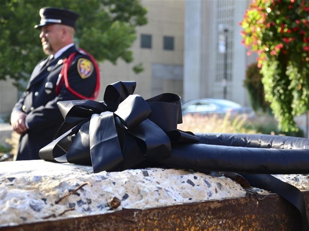 Bob Loviscek, president of Metropolitan Professional Firefighters Local 586, behind a piece of the World Trade Center placed outside the IU Auditorium, as part of the Ten Years Later: Indiana University Remembers 9/11 memorial service in 2011.