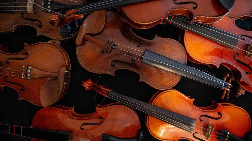 A pile of violins in need of repair at Dobie Middle School in Cibolo, Texas.