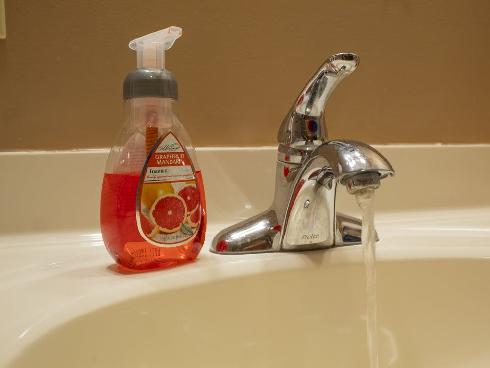 A soap dispenser sits next to a running faucet. IU psychology professor Jonathon Crystal says increasing hand washing can help slow the spread of the coronavirus.