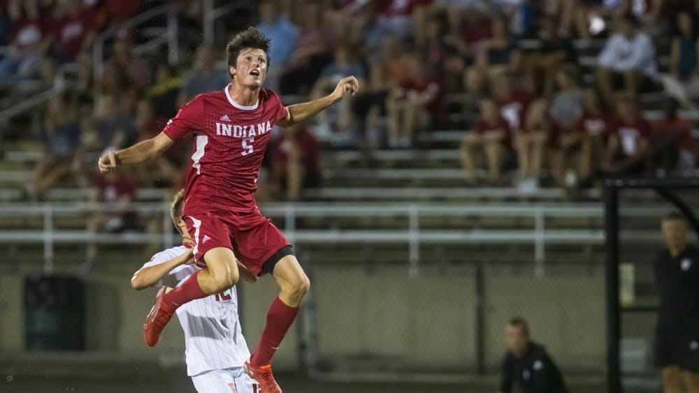 Redshirt-junior defender Daniel Munie jumps for the ball Sept. 17, 2021 at Bill Armstrong Stadium. Rutgers defeated Indiana 2-1.