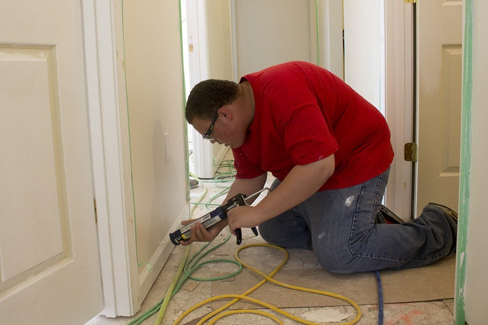 """Dante Hodge, 17, works on the baseboard inside his future house. His mother, Tracey Hodge, is the buyer of the house. He wasn't that excited as his mom, """"then we started putting the floor in, and I got super excited,"""" Dante said."""