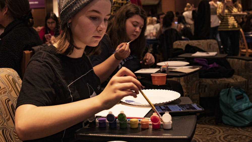 """Freshman Faith Buskirk dips her paintbrush at the Bob Ross Paint Along and Big Breakfast on Dec. 12 in the Indiana Memorial Union. """"I just love painting,"""" she said. """"Especially memes."""""""