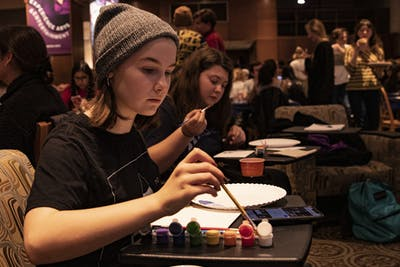 "Freshman Faith Buskirk dips her paintbrush at the Bob Ross Paint Along and Big Breakfast on Dec. 12 in the Indiana Memorial Union. ""I just love painting,"" she said. ""Especially memes."""