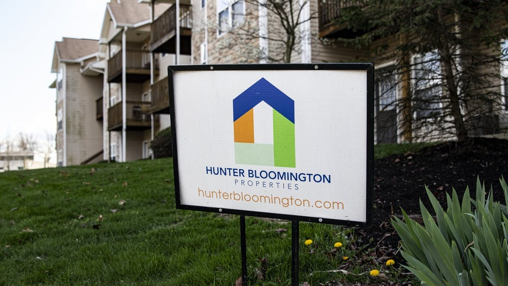A Hunter Bloomington Properties sign stands in the grass April 6 outside Bloom Apartments.