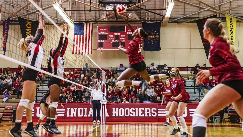 Junior middle blocker Deyshia Lofton jumps up to return the ball against two Rutgers defenders Oct. 13 at University Gym. Lofton ranks fourth in school history for solo blocks.