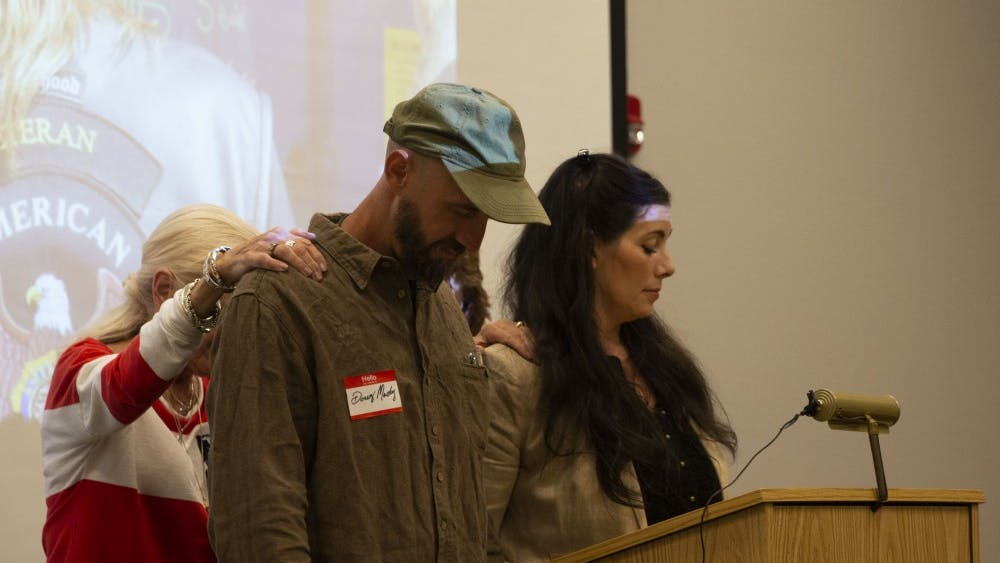Doug Mackey and his wife, Sarah Dye, are prayed over during a Grassroots Conservatives meeting Sept. 26 at the Ellettsville Branch of the Monroe County Public Library. Dye was invited to speak at the meeting about the issues surrounding her farm, Schooner Creek Farm, and the Bloomington Community Farmers' Market.