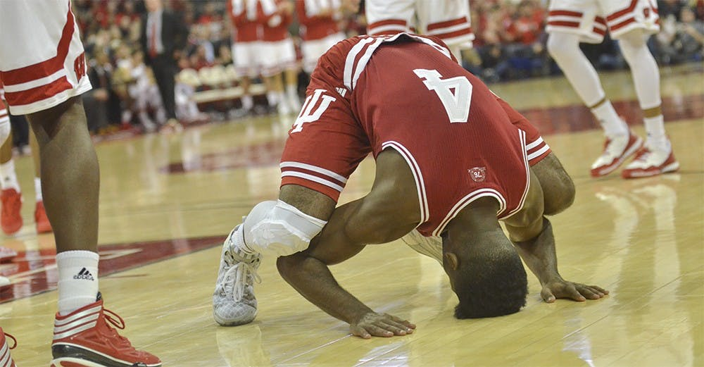 Sophomore guard Robert Johnson puts his head on the court after hearing the Hoosiers fouled Wisconsin on Tuesday at the Kohl Center. IU lost 82-79 in overtime.