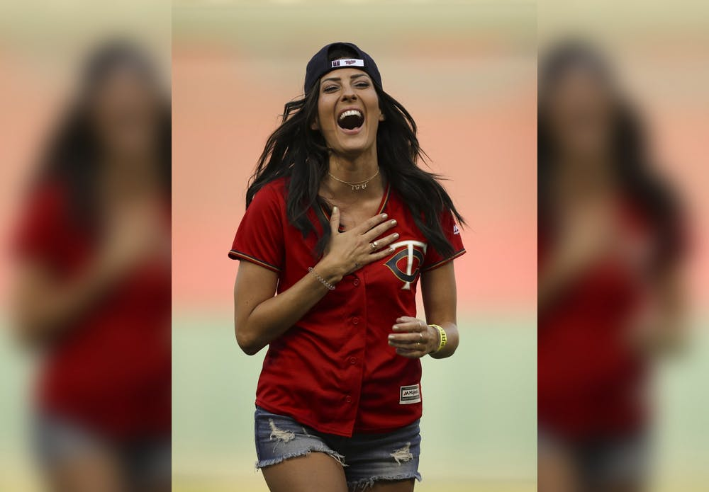 <p>Former Bachelorette Becca Kufrin reacts to Minnesota Twins left fielder Eddie Rosario after he handed her a rose after her ceremonial first pitch July 10, 2018, in Minneapolis, Minnesota. Kufrin and former Bachelor Ben Higgins will co-host &quot;The Bachelor Live on Stage&quot; on April 21 in Indianapolis.</p>