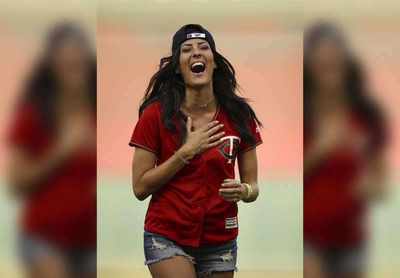 """Former Bachelorette Becca Kufrin reacts to Minnesota Twins left fielder Eddie Rosario after he handed her a rose after her ceremonial first pitch July 10, 2018, in Minneapolis, Minnesota. Kufrin and former Bachelor Ben Higgins will co-host """"The Bachelor Live on Stage"""" on April 21 in Indianapolis."""