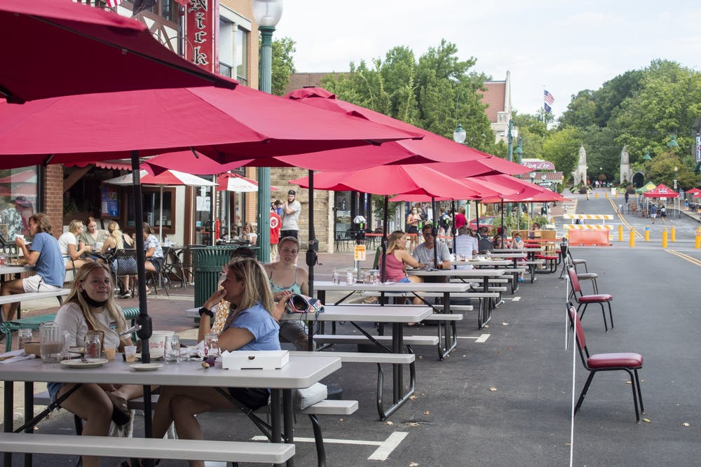 <p>Restaurant customers sit at tables Aug. 29, 2020, on Kirkwood Avenue. Some downtown Bloomington restaurants expanded outdoor seating into blocked-off parking spaces, or parklets, Wednesday.</p>