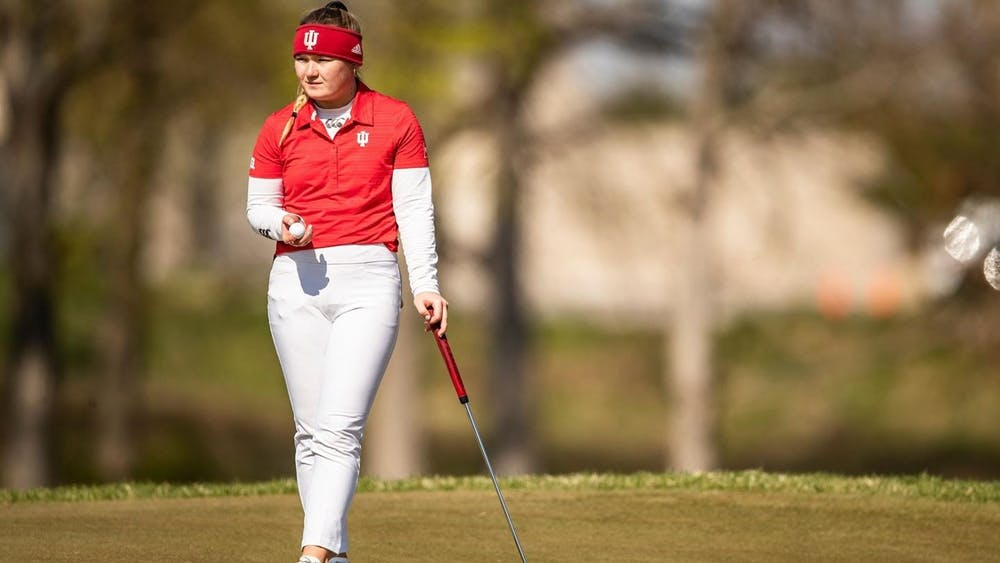 <p>Then-sophomore Valerie Clancy examines the course April 18, 2021, at the Pfau Course in Bloomington. Indiana finished its first tournament of the season in 14th.</p>