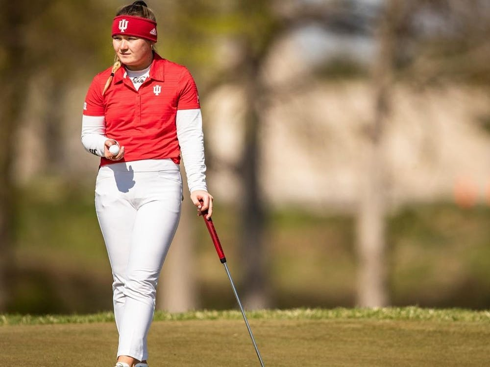 Then-sophomore Valerie Clancy examines the course April 18, 2021, at the Pfau Course in Bloomington. Indiana finished its first tournament of the season in 14th.