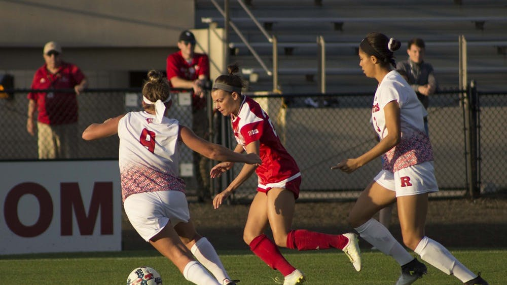 Sophomore midfielder Sydney Kilgore controls the ball under pressure from two defenders against Rutgers Saturday night. IU lost 1-0 in overtime to Rutgers at Bill Armstrong Stadium.