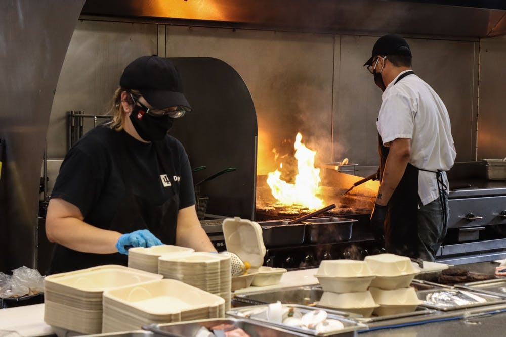 <p>IU Dining employee Cassi Abts puts food into boxes Aug. 29, 2021, at Wright Quad Dining Hall. The IU Dining website includes a disclaimer about current labor shortages. </p>