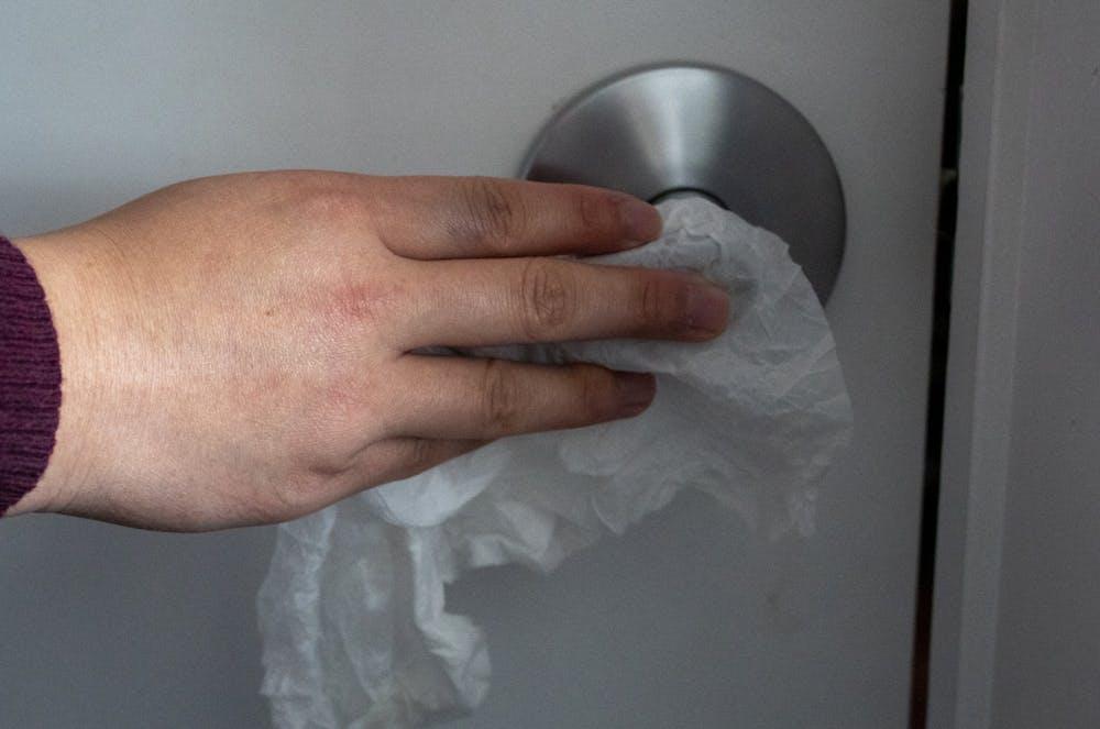 <p>An IU student cleans a doorknob with a Clorex wipe. </p>