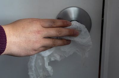 An IU student cleans a doorknob with a Clorex wipe.