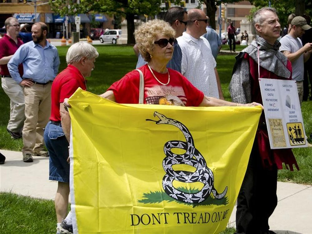 Greencastle resident Joan Billman holds a flag at a rally in opposition of a recent Indiana Supreme Court ruling prohibiting citizens from resisting police officers from illegally entering their homes Wednesday on the South Lawn of the Indiana Statehouse. Along with her husband Jack, Billman runs the Greencastle Defenders of Liberty, a Tea Party group.