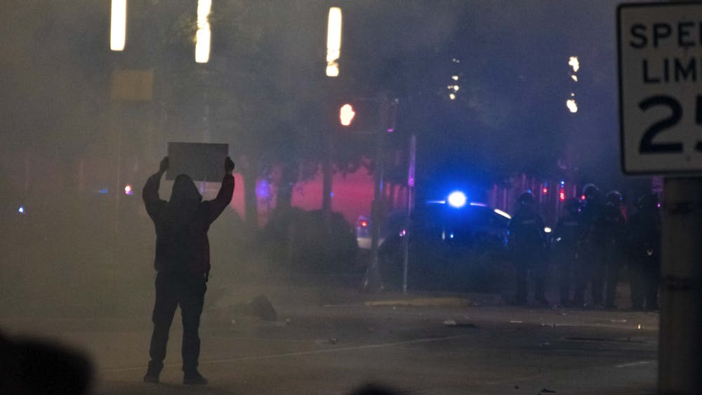 A protester holds up a sign in a cloud of tear gas as a line of police stand at an intersection May 30 in downtown Indianapolis.