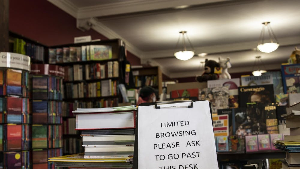"A sign reads, ""Limited browsing. Please ask to go past desk,"" on July 23 at the Book Corner bookstore. New rules have been put in place for book shoppers during the pandemic, including the addition of curbside ordering."