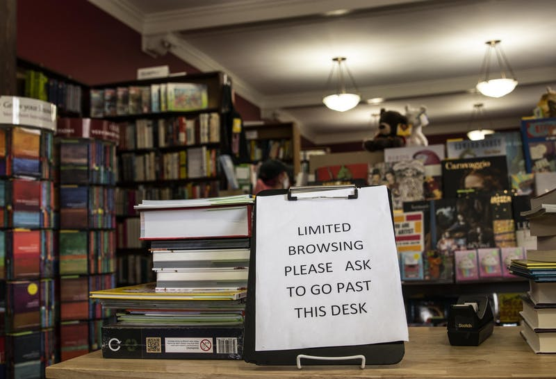 """A sign reads, """"Limited browsing. Please ask to go past desk,"""" on July 23 at the Book Corner bookstore. New rules have been put in place for book shoppers during the pandemic."""