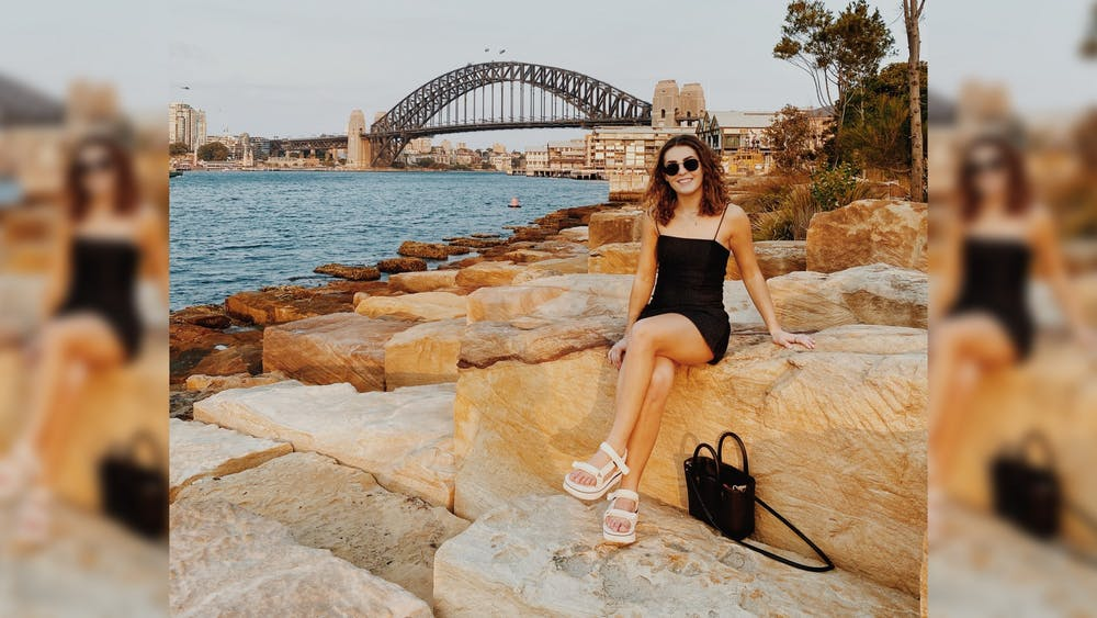 Junior Sydney Tomlinson sits on a rock Jan. 3 outside Sydney Harbour. Tomlinson is studying in Sydney, Australia, this spring.