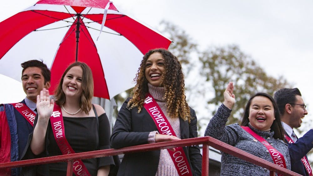 From left, 2018 Homecoming court sophomore Andres Ayala,  and seniors Maggie Hopkins, Olivia Malone and Angela Perez look at the crowd Oct. 12, 2018, during the Homecoming parade on Woodlawn Avenue.