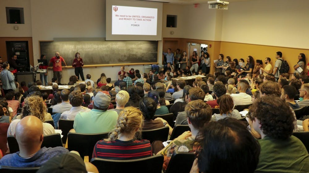 Students watch a presentation at the Indiana University Graduate Workers Coalition town hall Sept. 12 in the Lee Norvelle Theatre and Drama Center. The town hall addressed concerns raised by many graduate workers about the mandatory fees students are required to pay in order to work and learn at IU.