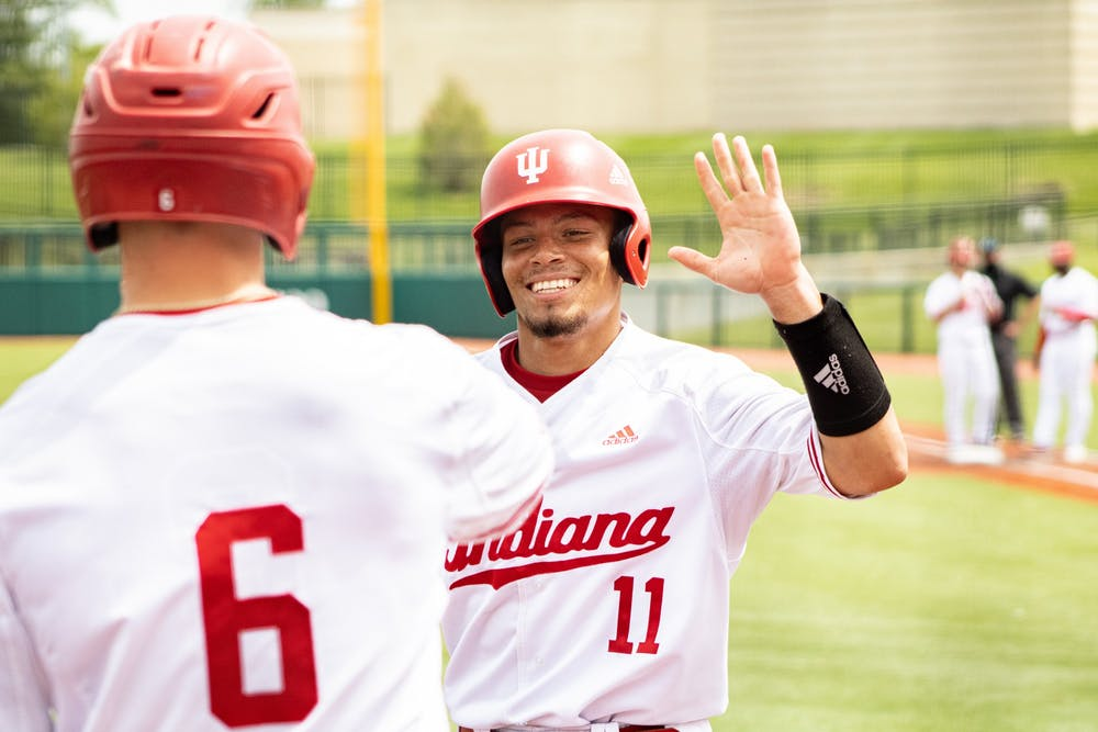 <p>Redshirt senior catcher Collin Hopkins high fives sophomore outfielder Grant Richardson after scoring against Iowa on Sunday at Bart Kaufman Field. The IU baseball team went 2-1 this weekend against Iowa at home. </p>