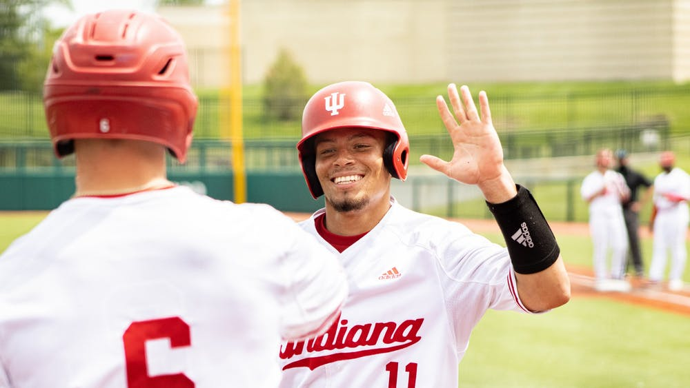 Redshirt senior catcher Collin Hopkins high fives sophomore outfielder Grant Richardson after scoring against Iowa on Sunday at Bart Kaufman Field. The IU baseball team went 2-1 this weekend against Iowa at home.