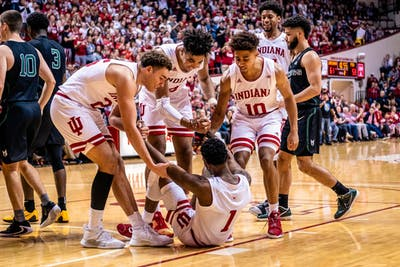 Teammates help junior Al Durham up after dunking a ball on Portland State University. IU defeated Portland State, 85-74.