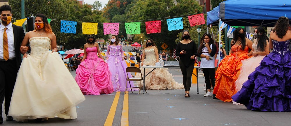 <p>The quinceañera dress models circle around the runway Sept. 26 on Kirkwood Avenue. Several wear hoop skirts under their dresses to make the gowns puff out more.</p>