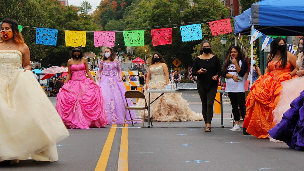 The quinceañera dress models circle around the runway Sept. 26 on Kirkwood Avenue. Several wear hoop skirts under their dresses to make the gowns puff out more.