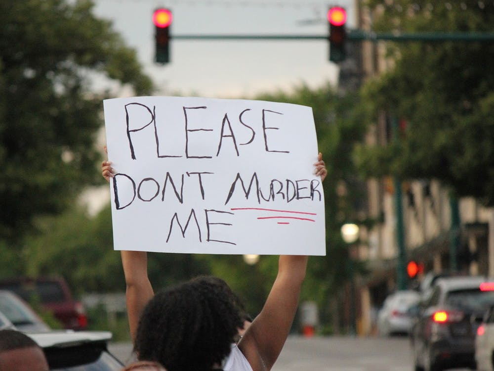 A protester holds up a sign June 1 in downtown Bloomington. Protesters marched through Bloomington in the wake of George Floyd's death at the hands of Minneapolis police officer Derek Chauvin.