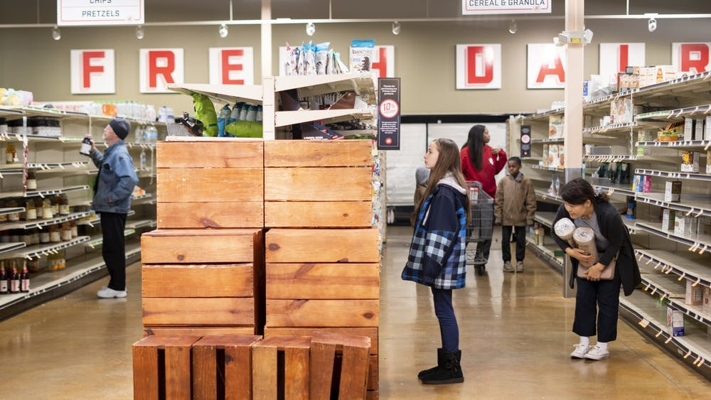 Customers shop and empty shelves Jan. 26 at Lucky's Market. The store is scheduled to close its Bloomington location Feb. 12.