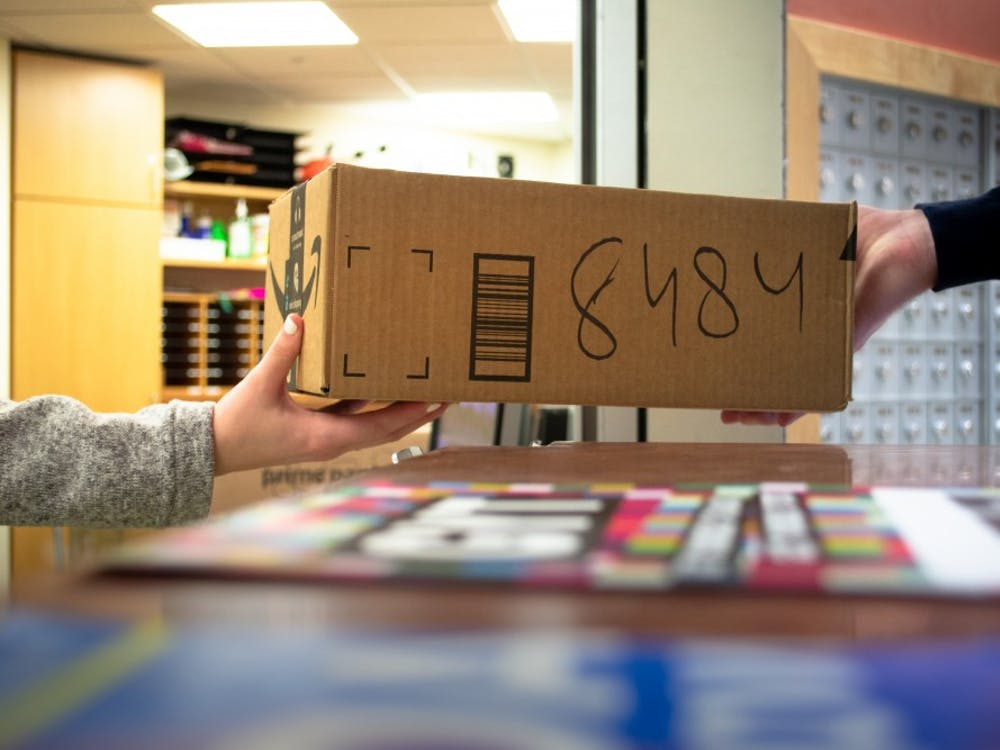 A center desk employee hands a package to a student. The U.S. Postal Service is trusted by drug dealers to ship narcotics nationwide, including to IU.