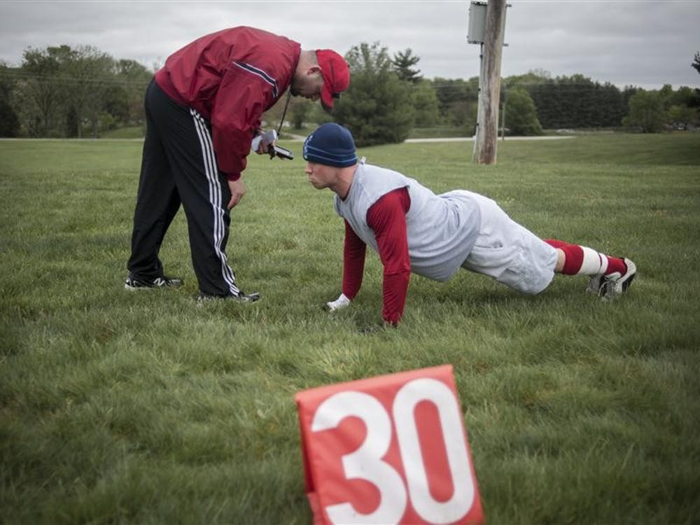 """McCool gives instructions to his captain Nick Land during the Cutters' first camp. Land's hamstring problems prevented him from rigorous directional running drills this early in the season. """"Gotta be doing something, coach,"""" Land says as McCool approaches. """"That's right,"""" McCool replies. """"Good man."""""""