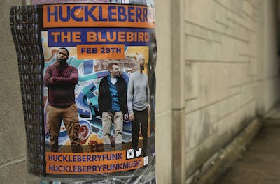 A Huckleberry Funk poster is wrapped around a pole Feb. 24 outside the Pourhouse Cafe. Huckleberry Funk is performing at 9 p.m. Feb. 29 in the Bluebird Nightclub.
