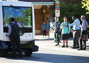 Pedestrians stop to peer into the self-driving bus and take pictures of it at its parked location on Kirkwood Avenue. EasyMile, a French autonomous vehicle maker, will be providing free rides in their EZ10 bus model to attendees on Friday from 10 a.m. to 4:30 p.m.