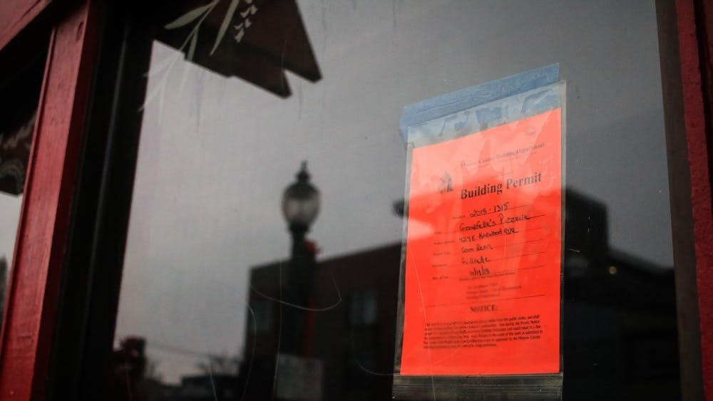 A building permit sign is posted on the window of Bluetique Bloomington on Nov. 29. Goodfella's Pizzeria will be opening a restaurant in place of the clothing store.