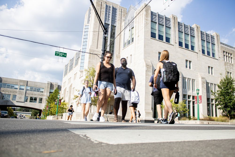 <p>Students cross the street Aug. 24, 2021, at the corner of North Fee Lane and East 10th Street.</p>
